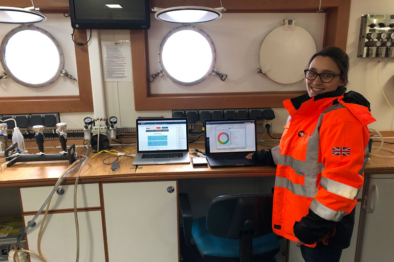 Emma setting up laptops and Nanopore MinION DNA sequencing equipment in lab onboard RRS Discovery ship