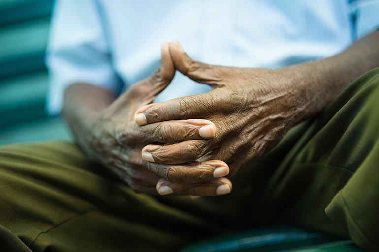 Image: An elderly man's hands clasped together showing wrinkles in the skin.